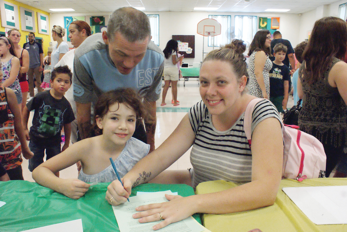 A FAMILY MATTER: Completing some paperwork at the Chester Barrows Elementary School during their Meet & Greet were Kristina, age 8, and her parents Elizabeth and Ray Caplette.