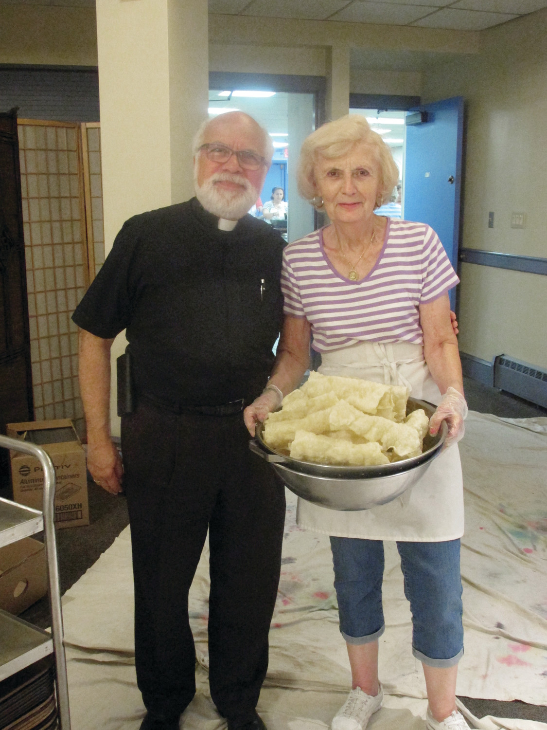 PROUD PAIR: Rev. Andrew George, pastor of Church of the Annunciation in Cranston, joins baking volunteer Melia Moschou who is carrying a full container of freshly made diples.