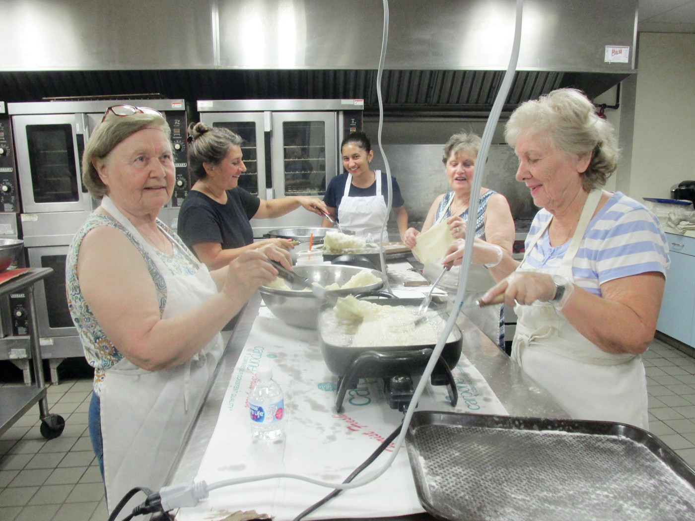 FRYING FAITHFUL: Armed with love for their church and their Greek heritage, volunteers Lisa Petrou, Anna Lekos, Adrianna Falcon, Roula Pryous and Anna Falcon fry the dough in individual old-time fry pans that later results in delicious diples.