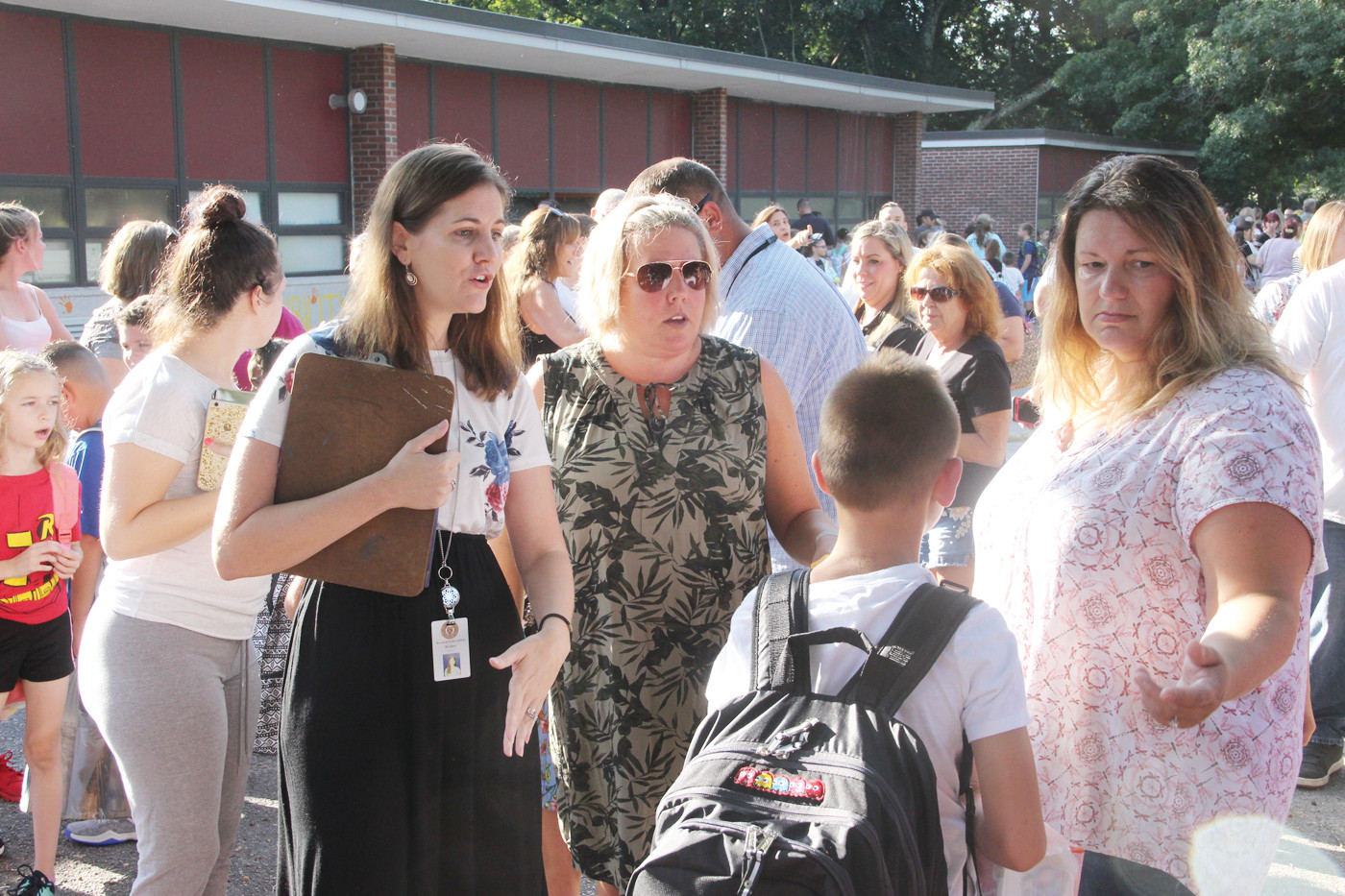 DIRECTING STUDENTS: Sherman school third grade teacher Kaitlyn Wallace is joined by PTO President Karin Kavanagh in the schoolyard to help students find their class.