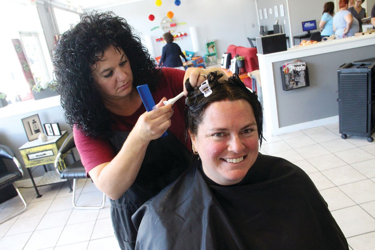 "OPEN FOR BUSINESS: Erin McCaughey enjoys the care of hair stylist Maria Tatarian at the outreach center Revive Hair Salon. A volunteer and partner at the center, McCaughey has distributed food from the center's general store to needy neighbors. ""We all take care of each other; that's community,"" she said."