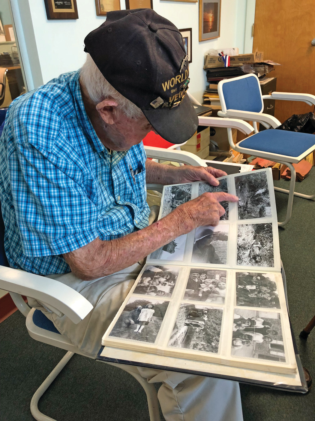 LIVING HISTORY: Sanford Tanner, 97 years old, flips through his photo albums at the Beacon headquarters on Tuesday. He joined the Army at 22 years old and landed in France on D-Day.