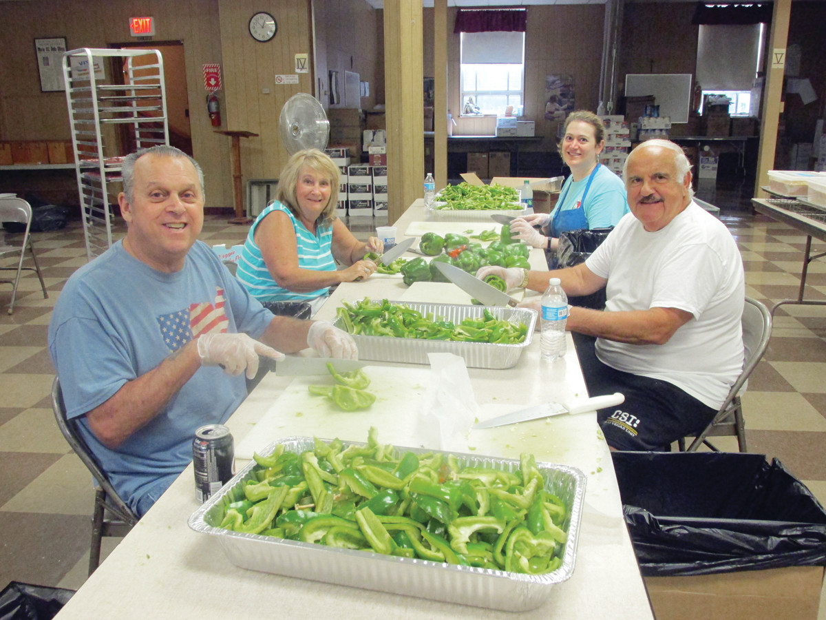 CARVING CREW: Our Lady of Grace parishioners like Steve Petrangelo, Linda Bessette, Laura Colannino and Don Rogue cleaned, carved and cut dozens of green peppers Tuesday that will be used for sausage and pepper sandwiches during this weekend's Feast and Festival in Johnston.