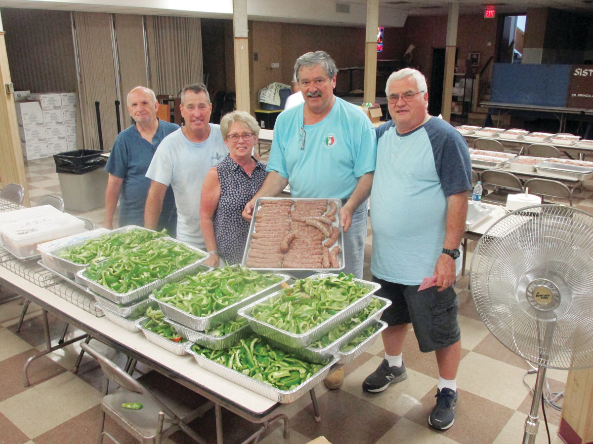 VALUABLE VOLUNTEERSS: Among those OLG volunteers who were preparing links of freshly-made Italian sausage Tuesday inside Fioretti Hall were, from left: Lou Pontarelli, Ron Geraghty, Joanne Burley, Al Colannino and Joe Quartino.