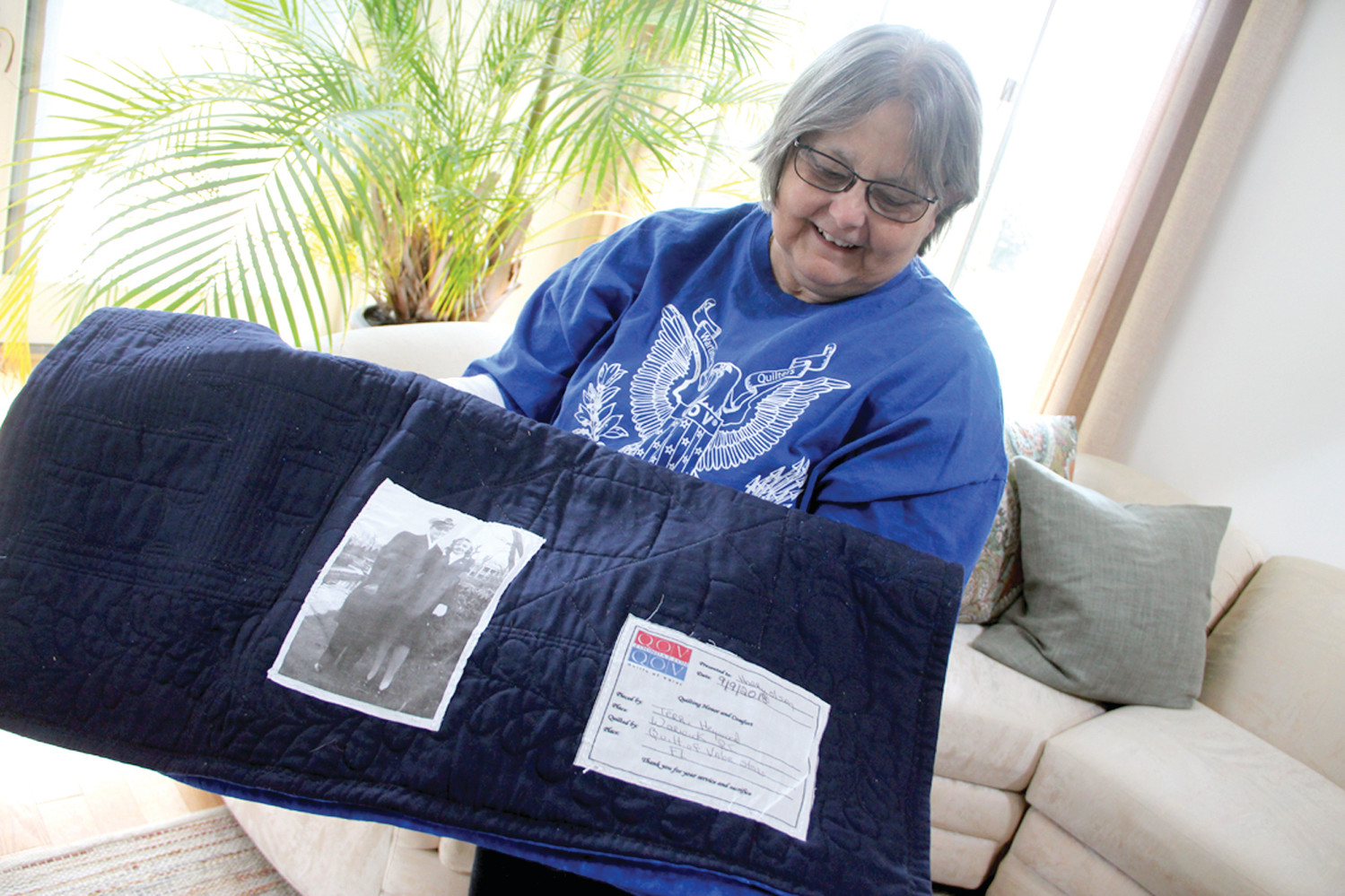 WITH SPECIAL MEANING: Terri Heywood of Quilts of Valor displays the back of the quilt she made for Harry Olsen with the picture of Harry and the woman he was to marry after WWII.