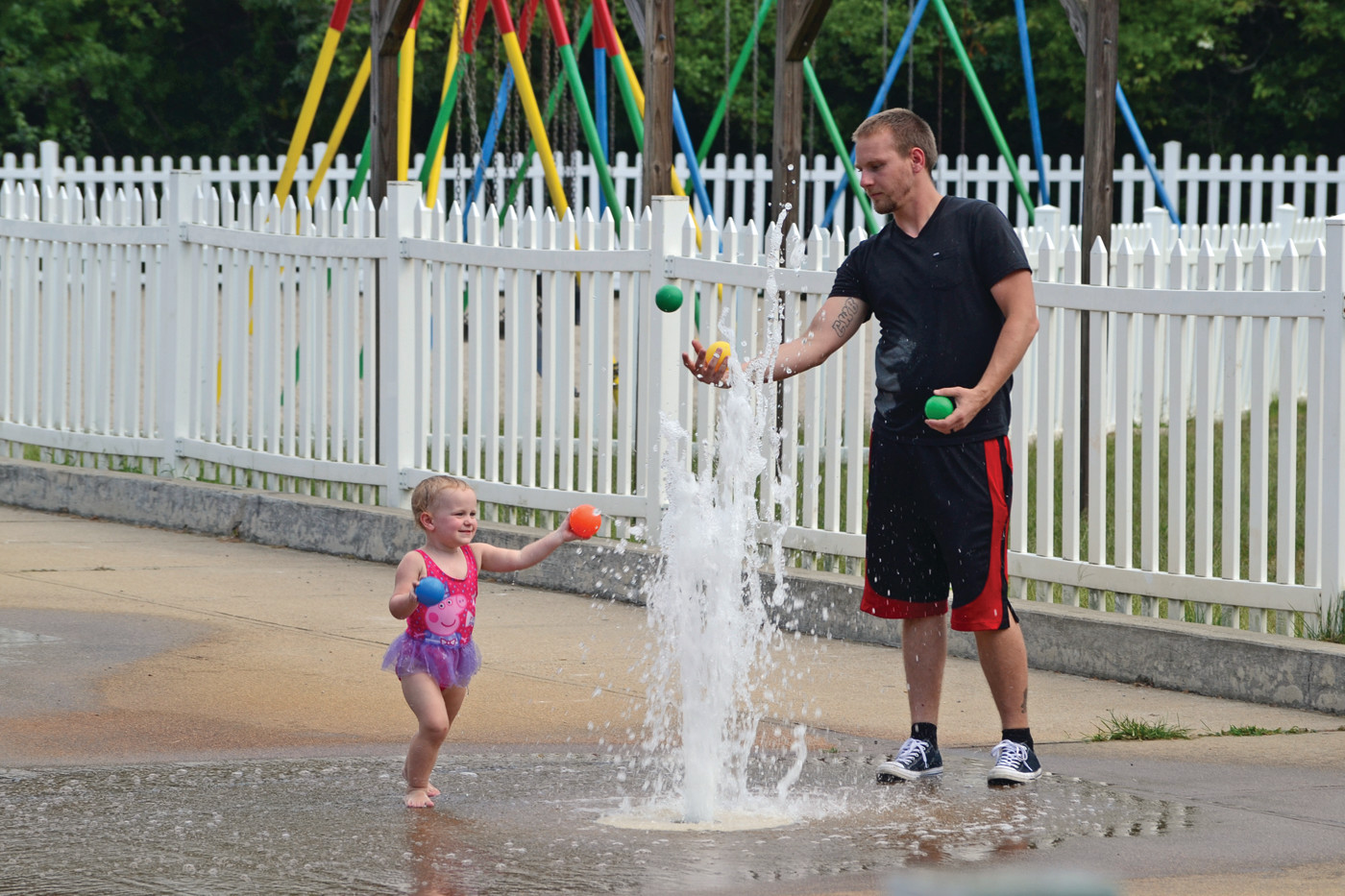 COOLING OFF: Nick Cheshier played catch with little Sophia Jones Thursday afternoon at the Kent County YMCA spray park.