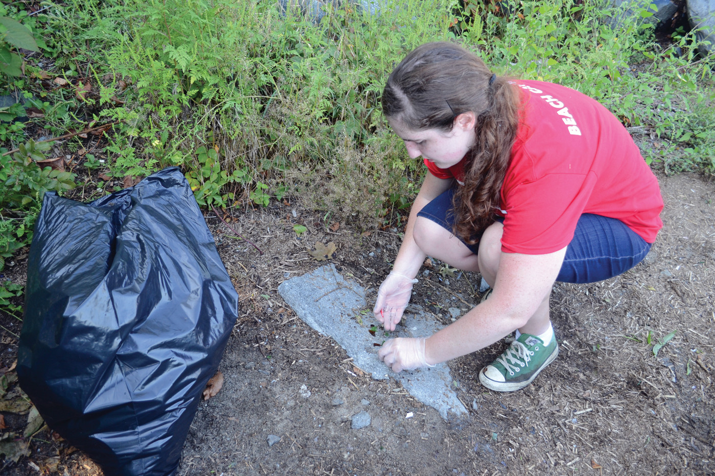 EVERY LITTLE BIT MATTERS: Debbie Woolley, working as part of a volunteer management coordinator internship with Save the Bay, picks up little shards of glass off a walking path at Salter Grove.
