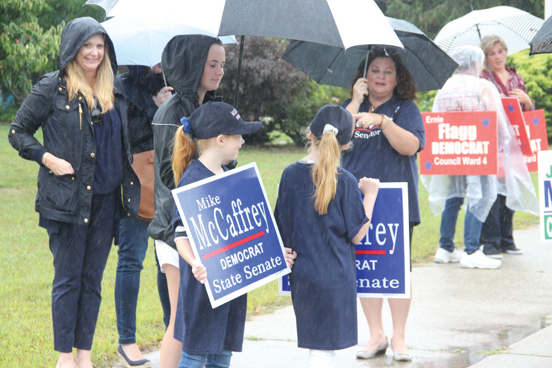 McCAFFREY CLAN: Family members turned out in support of Senator Michael McCaffrey, seen here taking cover under umbrellas at Hoxsie School.