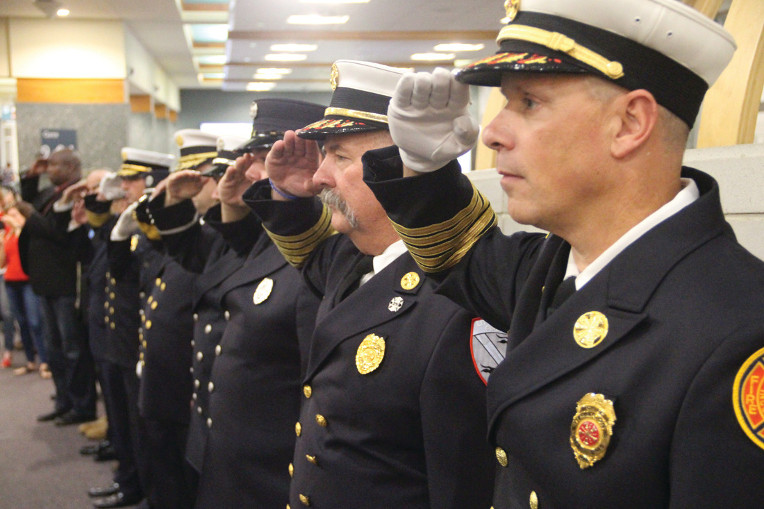 PAYING TRIBUTE: Retired and current members of Rhode Island fire departments saluted the veterans as they were led to their departure gate by the Providence Police Pipes and Drums.
