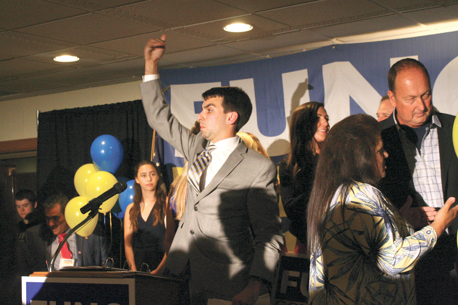BUSY MAN: Fung's press secretary, Andrew Augustus, sets up the stage before the gubernatorial candidate came out to make his primary victory speech.