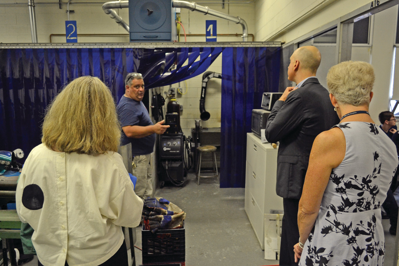 A GLIMPSE BEHIND THE CURTAIN: Marine Trades instructor Christopher Bianco shows a group of administrators, including RIDE Commissioner Ken Wagner and Deputy Commissioner Mary Ann Snider, along with guidance director Ann Hourahan, one of the welding stations in the marine trades workshop.