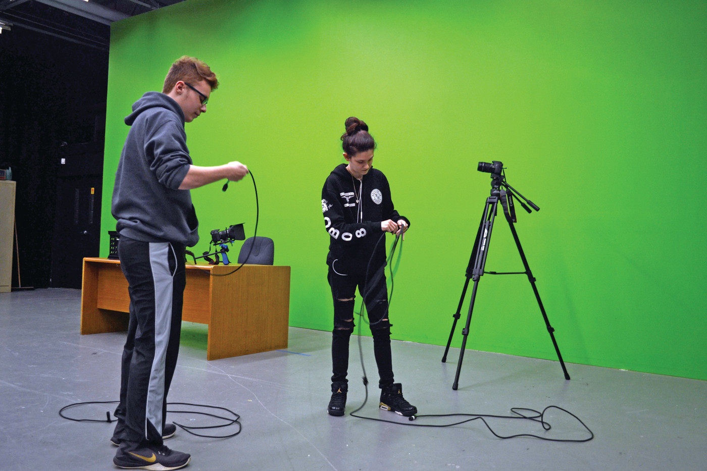WRAP IT UP: Adam Rega and Halie Papa race to see who can wrap up a length of cording neatly and correctly first. Behind them is the enormous green screen, which is the creative and practical result of a large wall painted bright green.