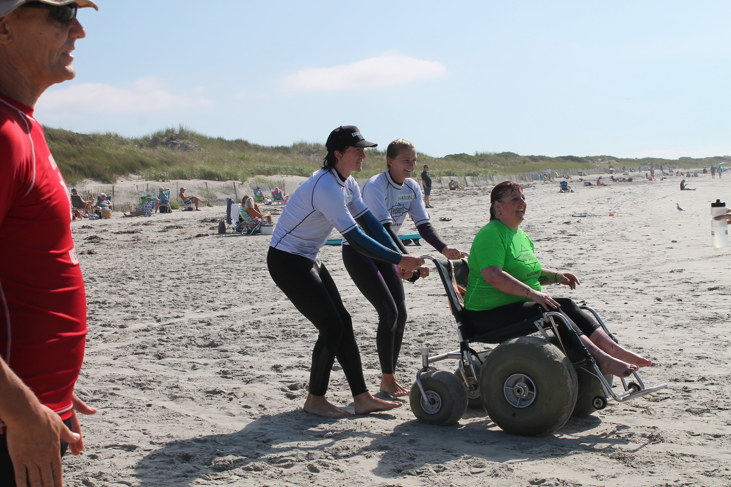 "AmpSurf volunteers leading Tina Pedersen, a.k.a. ""Miss Wheelchair RI"", to the water's edge to prepare for an unforgettable surfing experience."