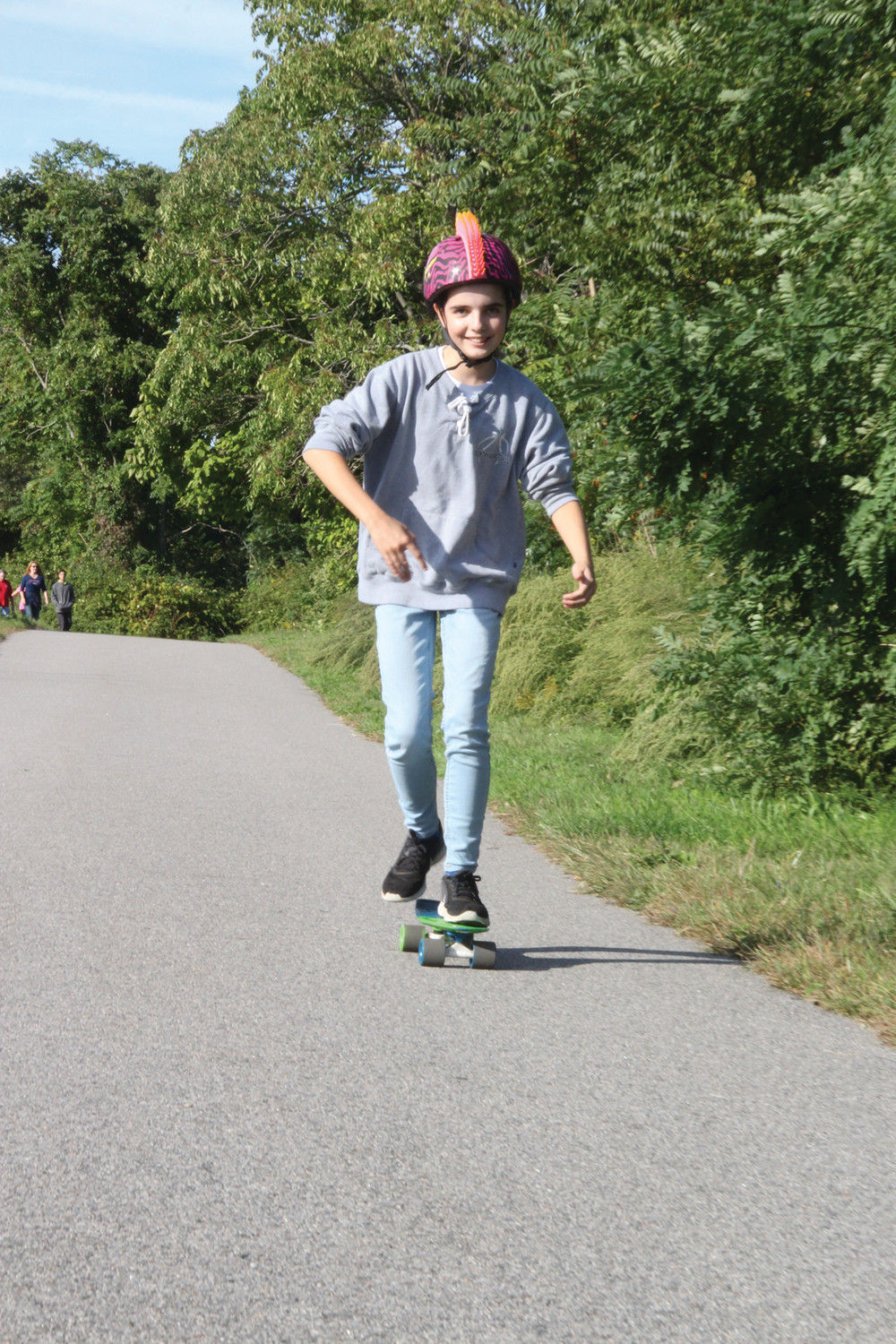 POINT ON A ROLL: Coventry residents Lilly Ancil and her mother Laura traveled the park path. Lilly, wearing a helmet in the shape of a Mohawk cut, did it on her skateboard.
