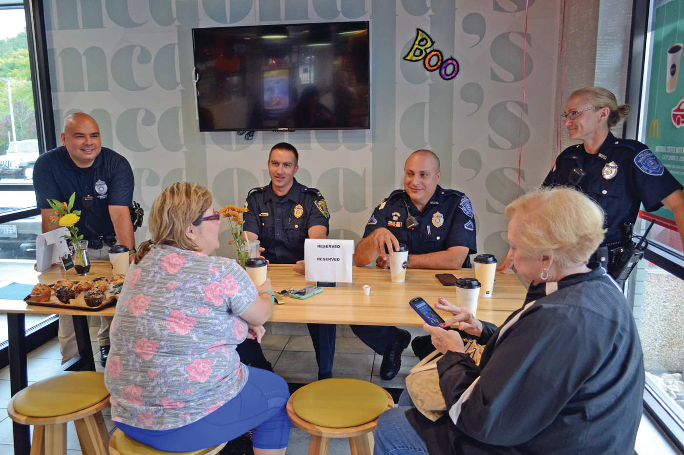COPS AND COFFEE: Officers Mark Jandreau, Capt. Ryan Sornberger, Matt Moretti and Jill Marshall talk with Carol Sanquist (front right) and Bethany Hashway (to her left) during the Coffee with a Cop event held at McDonald's on Post Road in Warwick on Wednesday.