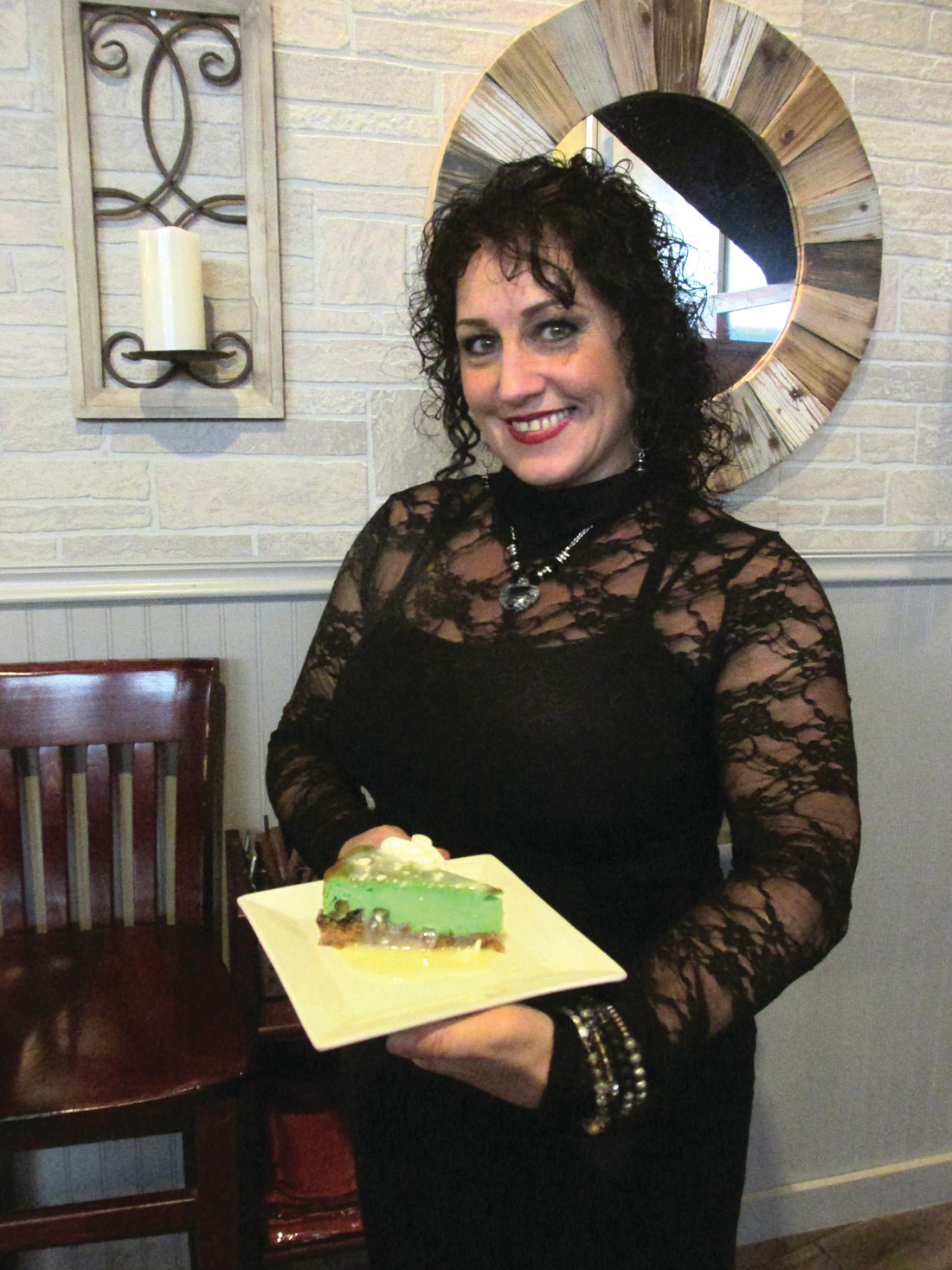 CLEVER CREATION: Susie Marshall, a super staffer at The Ave Restaurant Bar & Grill, holds a serving of Pistachio Cheesecake, one of Chef-Owner Jennifer Lombardo's creations.