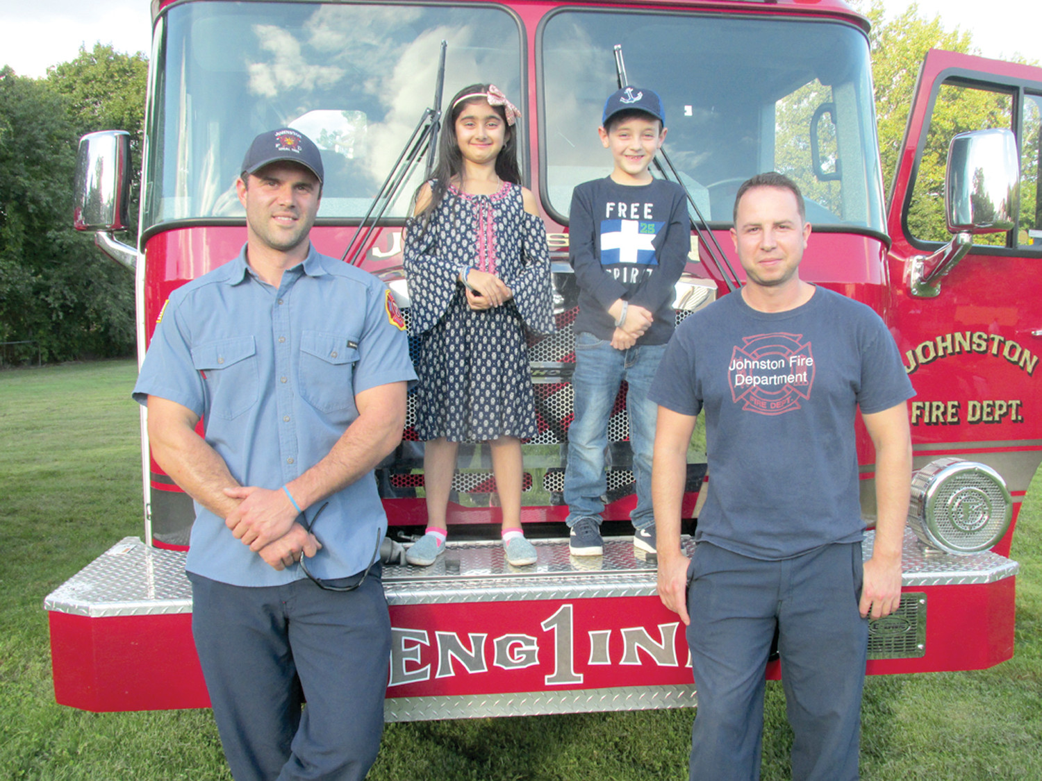 DELIGHTFUL DUTY: Johnston Firefighters like Justin Petrin (left) and Ray Cianci made last Saturday's Touch-A-Truck event special for youngsters like Samaira Dhamija and Flynn Merlino who are all smiles while being photographed by their parents at St. Rocco's School.