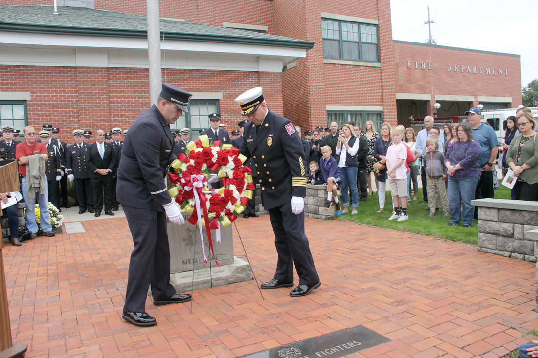 PLACING OF WREATH: Rescue Lt. Michael Carreiro, president of the firefighters union and Acting Chief Marcel Fontenault Jr. place a wreath in front to the memorial marker.