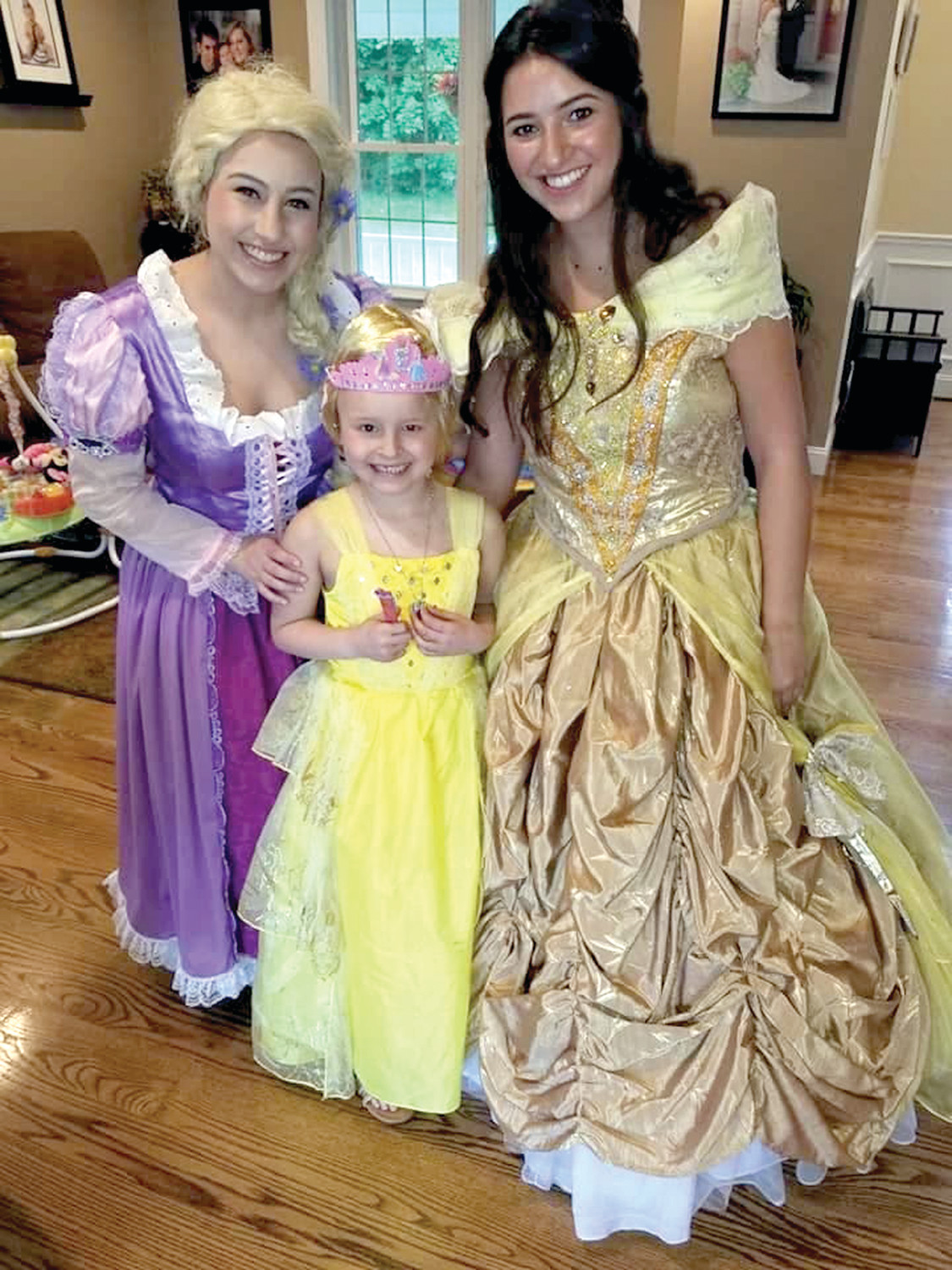 "AN IMPACT ON HER: Megan Mahoney, left, could not have imagined the impact that her business, ""Meg's Princess Parties"" would have on children who were battling life-threatening illnesses, nor could she have known the impact that performing for these children would have on her.  Here she is with one of the birthday girls in the middle, as well as Carrie Minassian, as Belle, on the right."