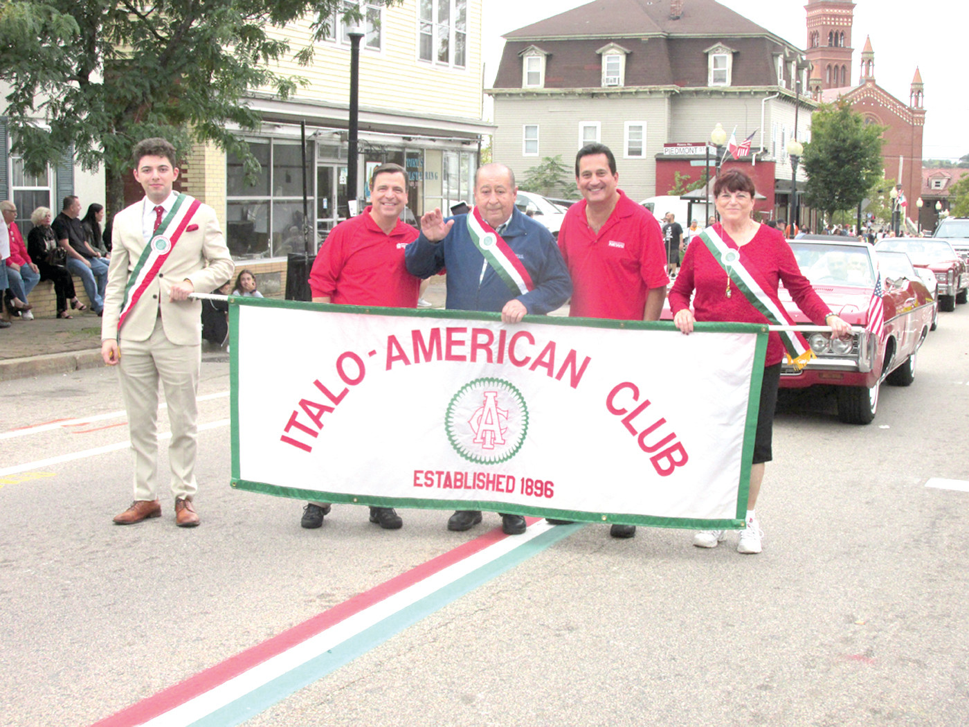 PROUD PACK: Johnston residents Carmine DeRobbio (center), Linda Folcarelli and Ron Giorgio honored their Italian-American heritage by carrying the Italo-American Club's banner in Sunday's Columbus Day Parade. They're joined by WPRI-TV personalities Tony Petrarca and Mike Montecalvo.