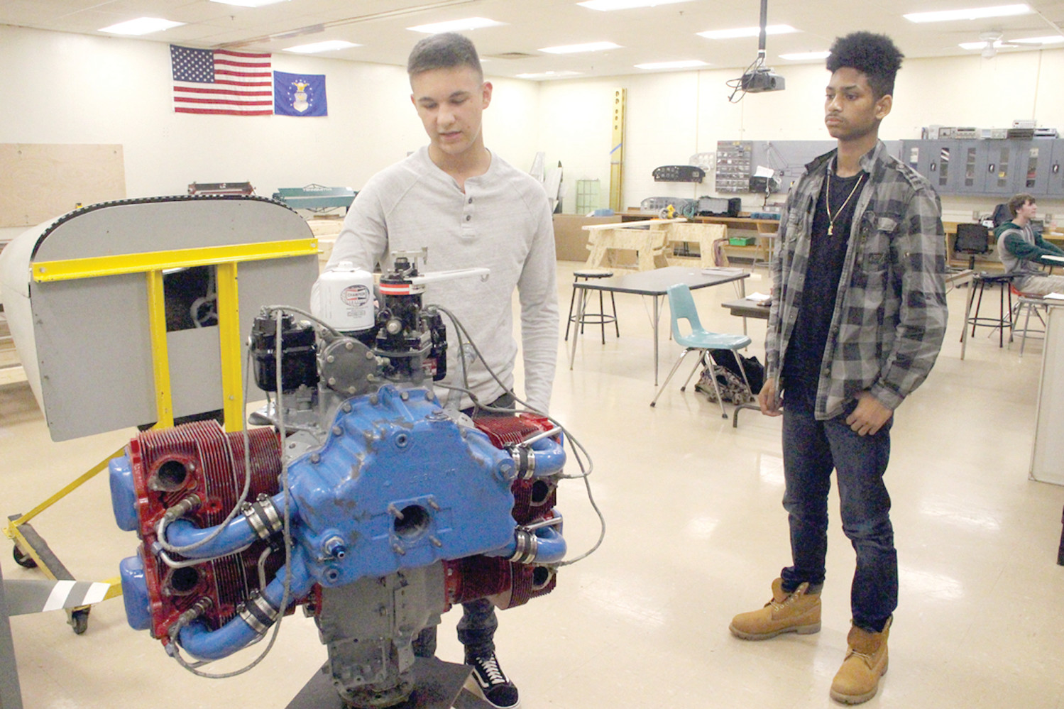 HE KNOWS HIS ENGINE: Sophomore Andrew Clark points out components to the aircraft engine in the classroom as Nick Sevrino looks on.