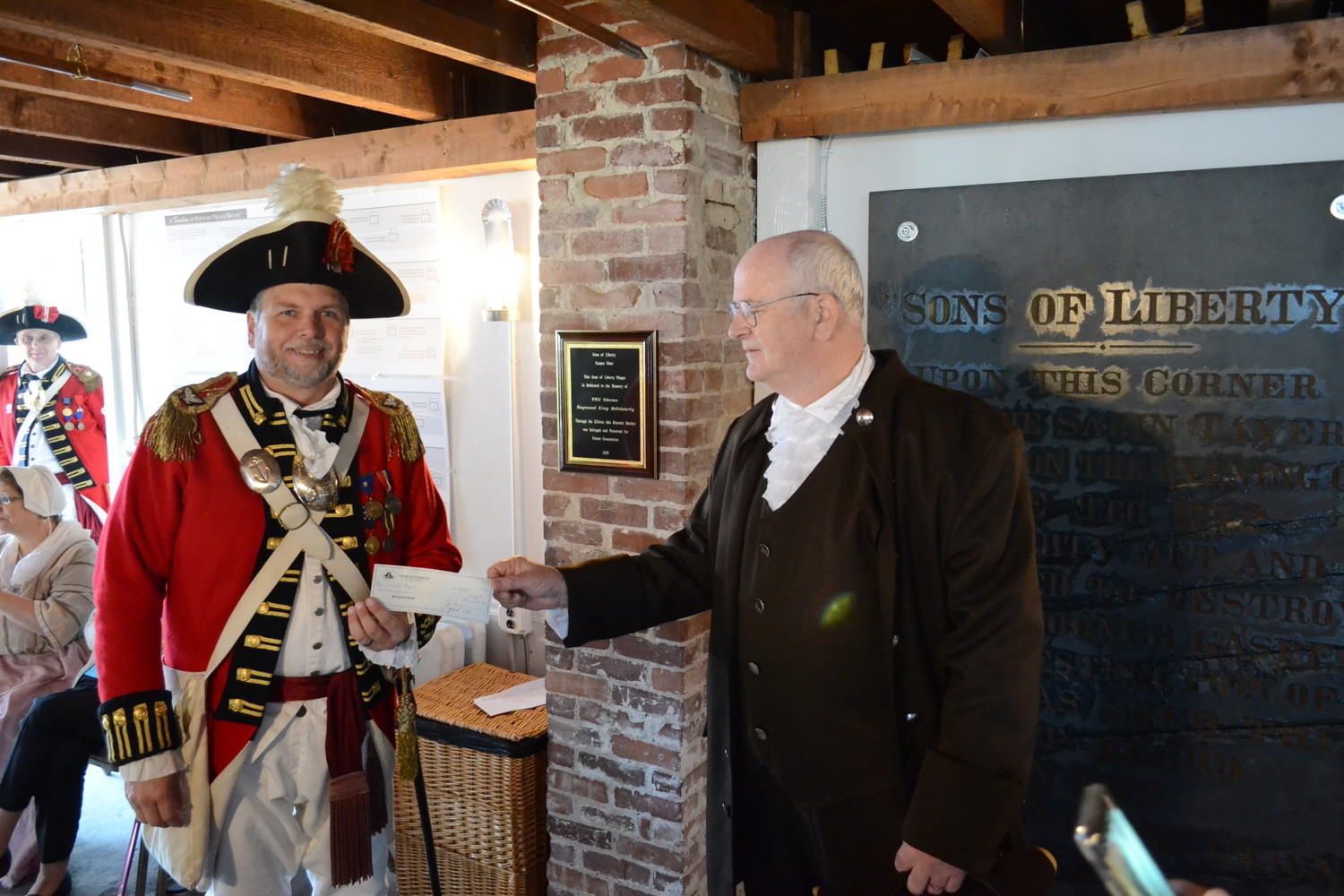 TO HISTORY: Dr. John Concannon presents a check for $500 to Colonel Ron Barnes, Commander of the Pawtuxet Rangers, towards the cost of moving and mounting the heavy historic plaque.