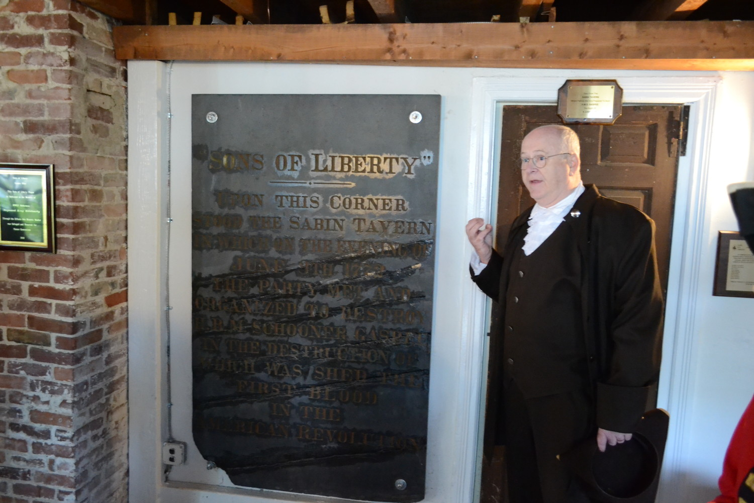 A CLEAN (OLD) SLATE: Dr. John Concannon, historian for the Gaspee Days Committee, speaks about the history of the Sons of Liberty in front of the plaque that has the organization inscribed upon it, illustrating that the revolutionary group had a hand in the burning of the Gaspee.