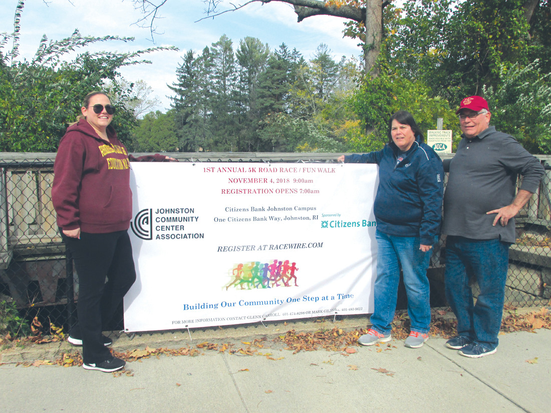 FAMILY FUN: The Carroll family – Nicole (left), her mother Ann and father Glenn – who have long been involved with the Johnston Community Center Association, finish hanging the promotional banner on the War Memorial Park fence for the non-profit's first-ever 5K Road Race/Fun Walk that will be sponsored by Citizens Bank.