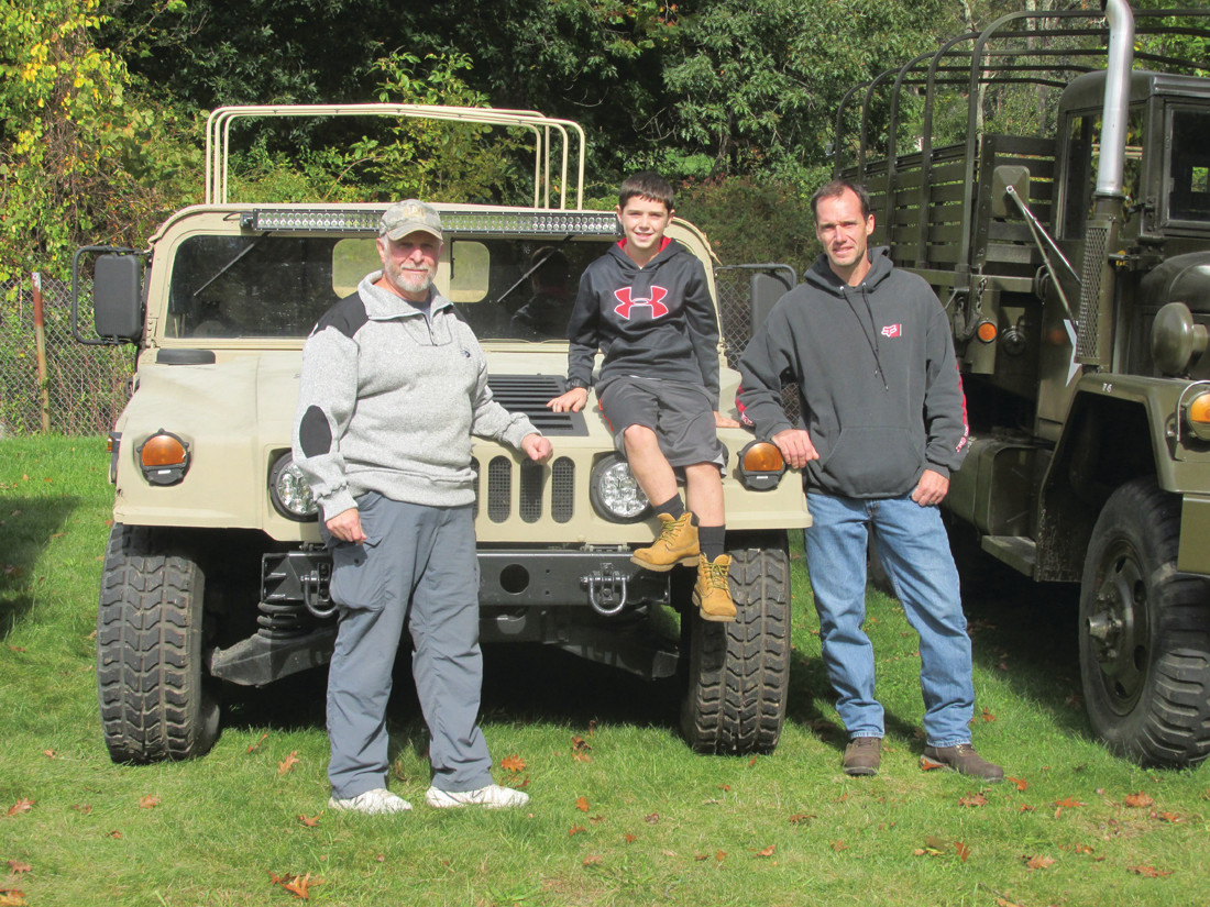 TRAVIS' TRIP: Neal Travis, 10, and his father (right) enjoy a fun moment along with Wayne Martini (left) who brought a number of his old-time U.S. Army vehicles to the Ocean State Vintage Haulers show Sunday in Cranston.