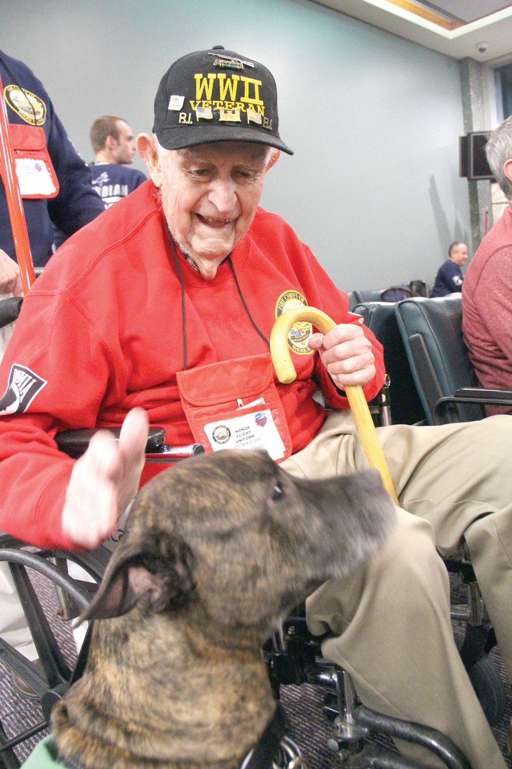 COMPANION FOR A MOMENT: WWII veterans Sanford Tanner of Warwick greets Teddy of the PVD Pups program while waiting for the departure of Saturday's flight.