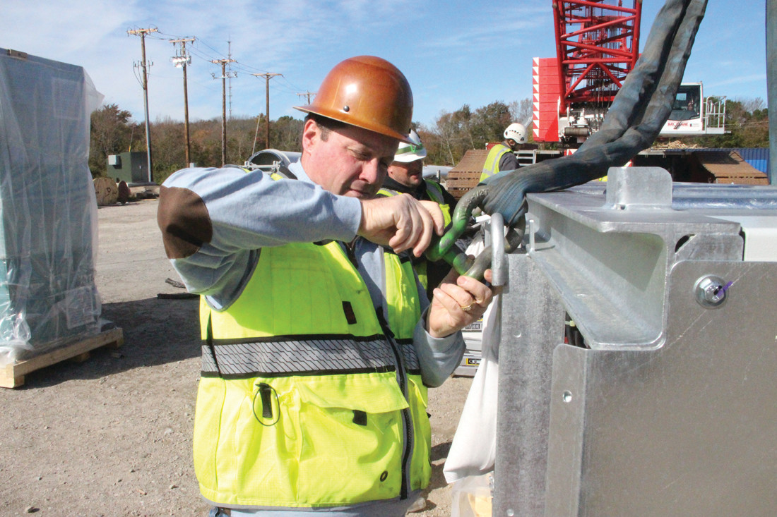 ON THE JOB: Mark DePasquale affixes a shackle before a crane lifts instrumentation panels into place.