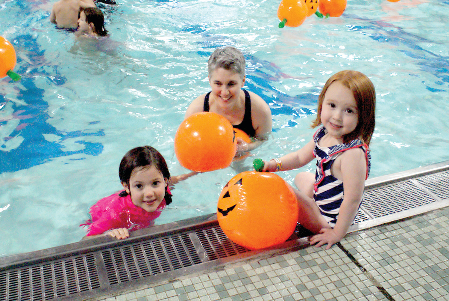 PICKING PUMPKINS: Pictured are Reese, age 7 and Riley Burgess, age 4, enjoyed their time during Swim with the Pumpkins with their mother, Jennifer Kodis at the Cranston YMCA.
