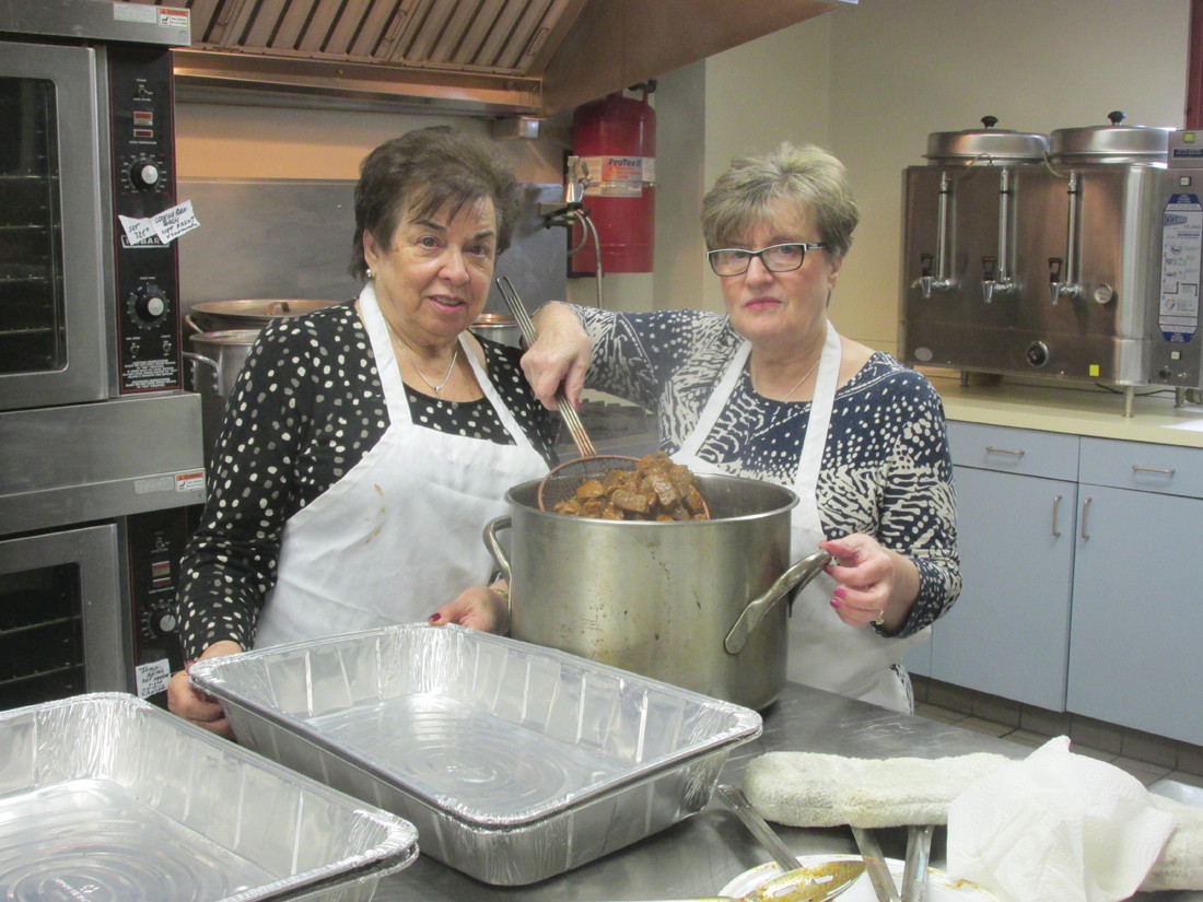 SUMPTUOUS SERVING: Bessie Papigiotis (left), who has been making Stifatho – a.ka. Greek Beef Stew – for the Ladies Philoptochos Society's Greek Food Fair & Christmas Bazaar that will be held in Cranston this weekend, helps prepare another batch with Roula Proyous during last Friday's cooking session.