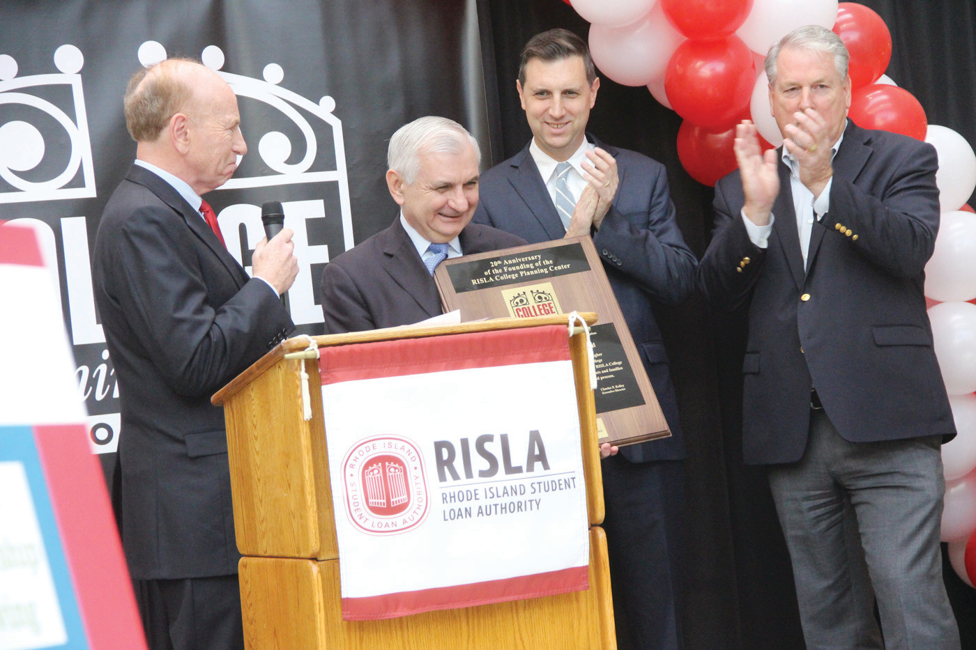 CHEERS: Senator Jack Reed accepts a plaque in recognition for his role in establishing the College Planning Center at Tuesday's anniversary celebration. With him from left are Charles Kelley, executive director of the RI Student Loan Authority; General Treasurer Seth Magaziner and RISLA board chair Robert Delaney.