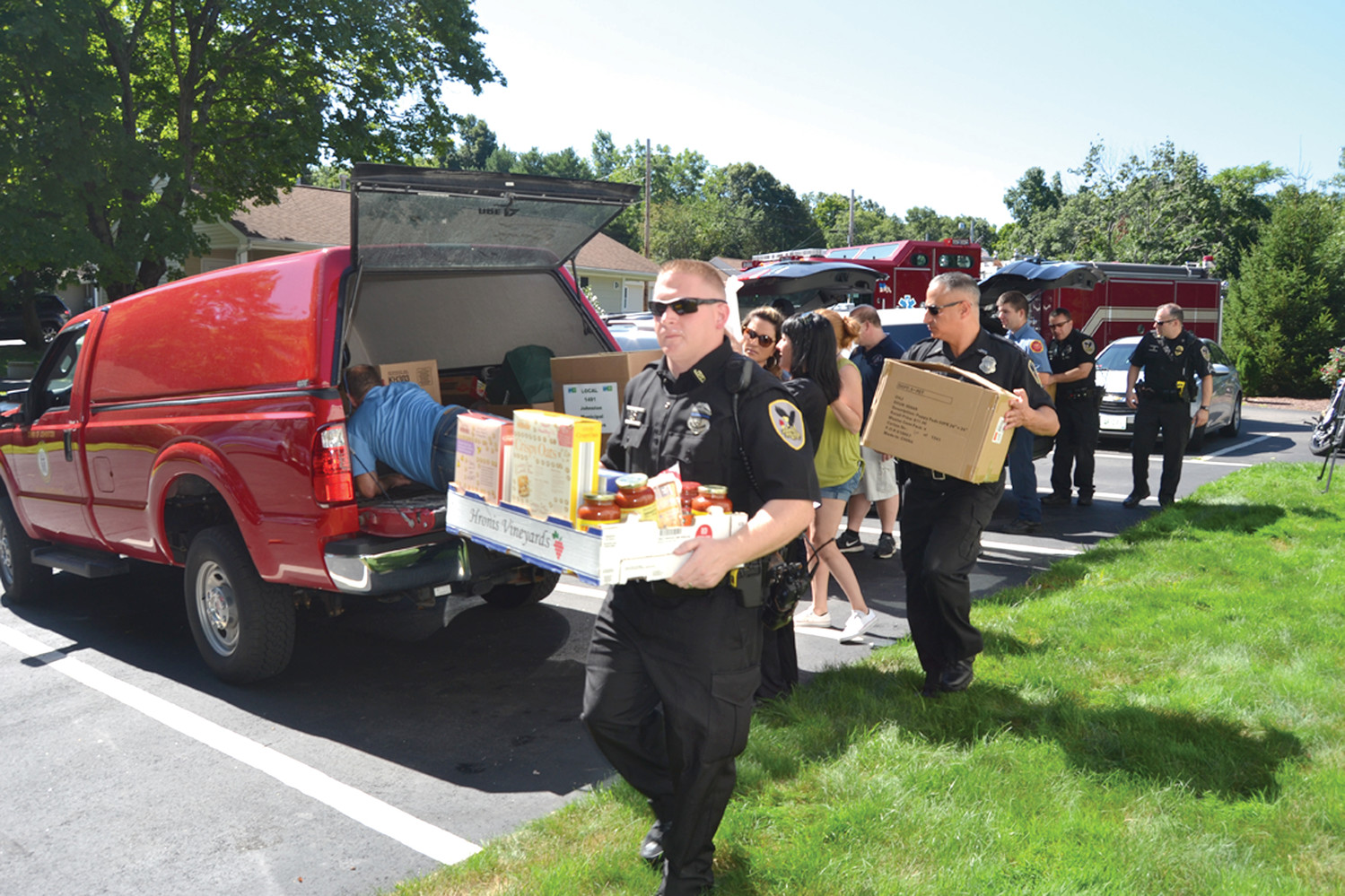 BRINGING IT IN: In August, members of the Johnston Police Department, Johnston Fire Department, and town workers delivered hundreds of pounds of food that they collected for veterans in need at Johnston's own Operation Stand Down Rhode Island after their pantry shelves were nearly empty. (Sun Rise photo by Tim Forsberg)