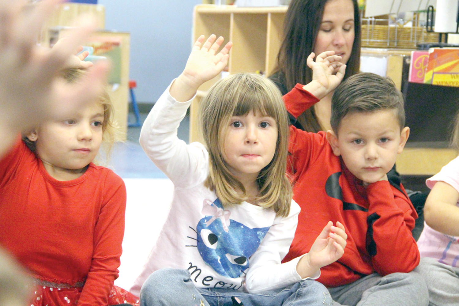 AWED BY AN AUTHOR: Westbay Children's Center pre-school students Layla Dureault, Eleanor Cotter Grayson and Gabriel Luna were tuned into the story being read by Linda Brennan.