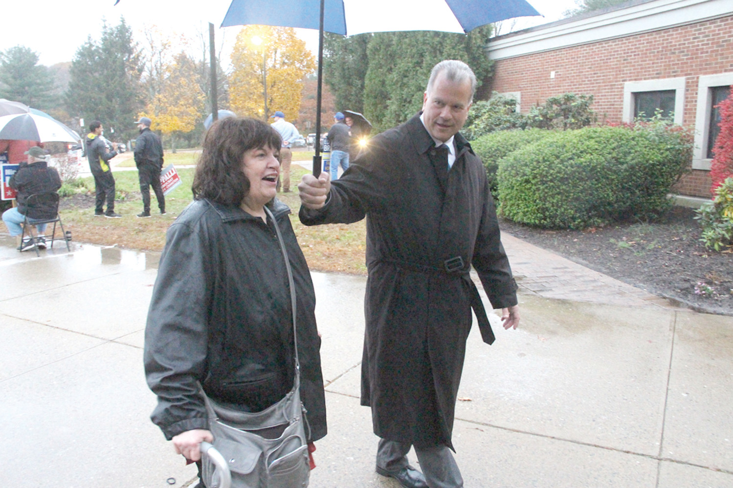 LENDING A HAND IN THE RAIN: Nicholas Mattiello, Democrat candidate for House Dist. 15 and current Speaker of the House, was also as Hope Highlands Tuesday afternoon, here helping Mary Lombardi to the front door of the Western Cranston polling location.