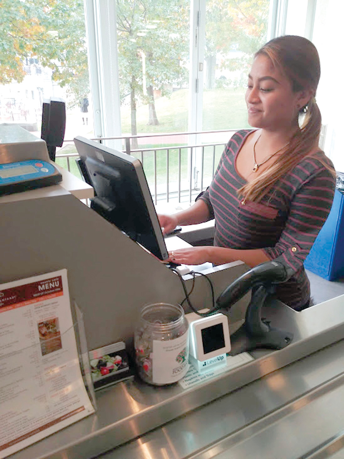 READYING FOR THE RUSH: Intern Gabby Warren is at the cash register inside of the BCBSRI cafeteria as the midday lunch rush is about to start.