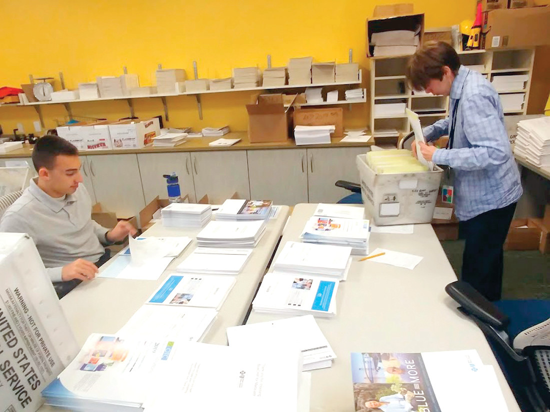 IMPORTANT WORK: Both Tom Marcello and Nikolas Simijis are hard at work creating folders filled with important information for BCBSRI's open enrollment period. Their work is detail-oriented and together they assemble hundreds of folders, making them ready for mailing.