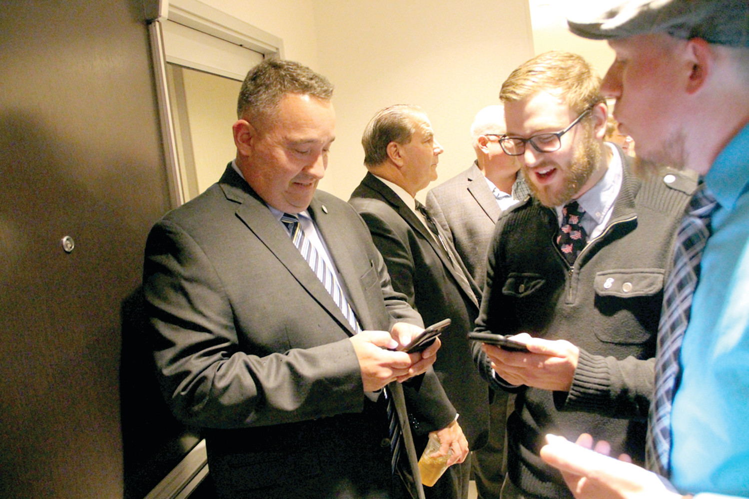 RESULT ORIENTED: Ward 3 Councilman Tim Howe, who was unopposed, and District 1 School Committee candidate Kyle Adams, who beat Richard Cascella, use their cell phones to retrieve election results.