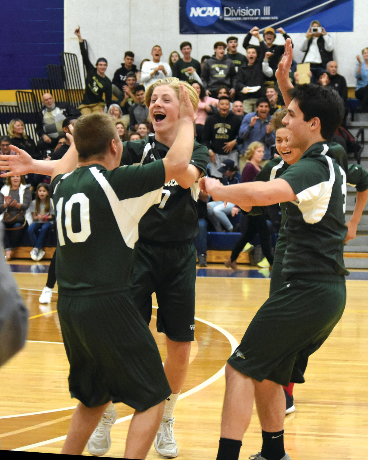 Bishop Hendricken unified volleyball players Aidan Lawton, Cam Toussaint and Brian Schattle celebrate during the team's state championship win over Portsmouth.