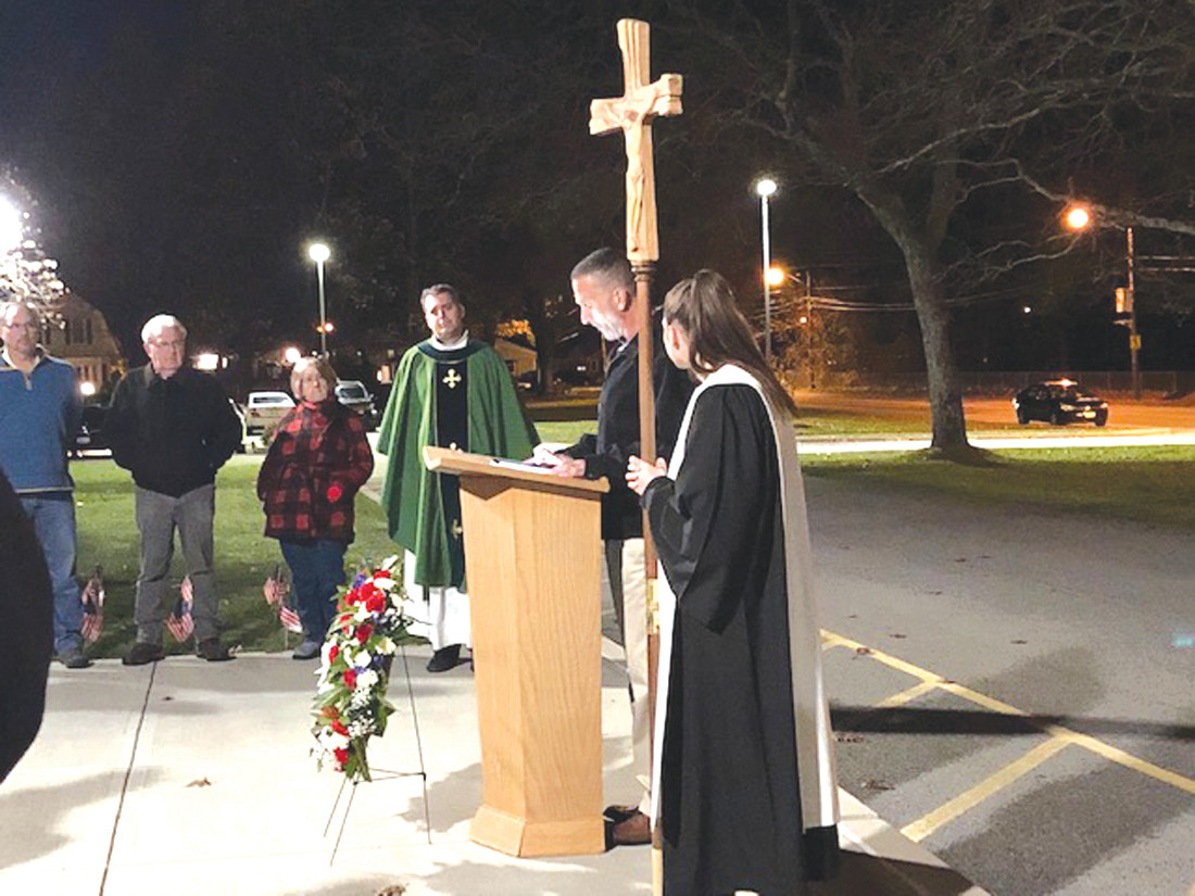 CONDUCTING CEREMONY: Fr. Matt Glover is pictured with John Macera, who read the names of the veterans and altar server (holding the cross) Mackenzie Puckett.