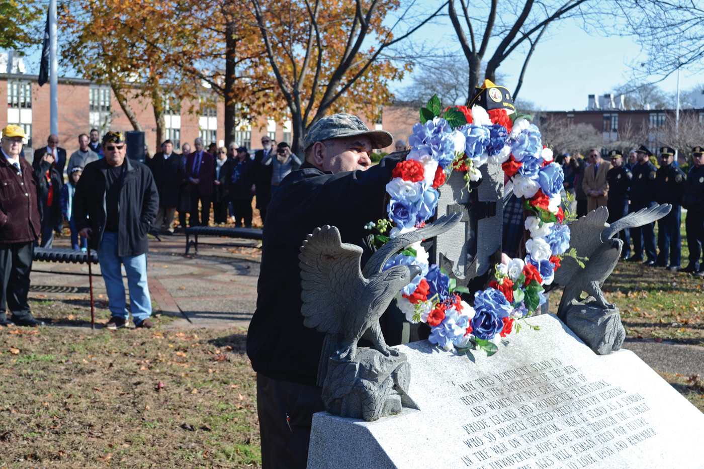 A SYMBOLIC GESTURE: Anthony Rodrigues, president of the Warwick Veterans Council, lays the ceremonial wreath on the memorial dedicated to Rhode Island service members.