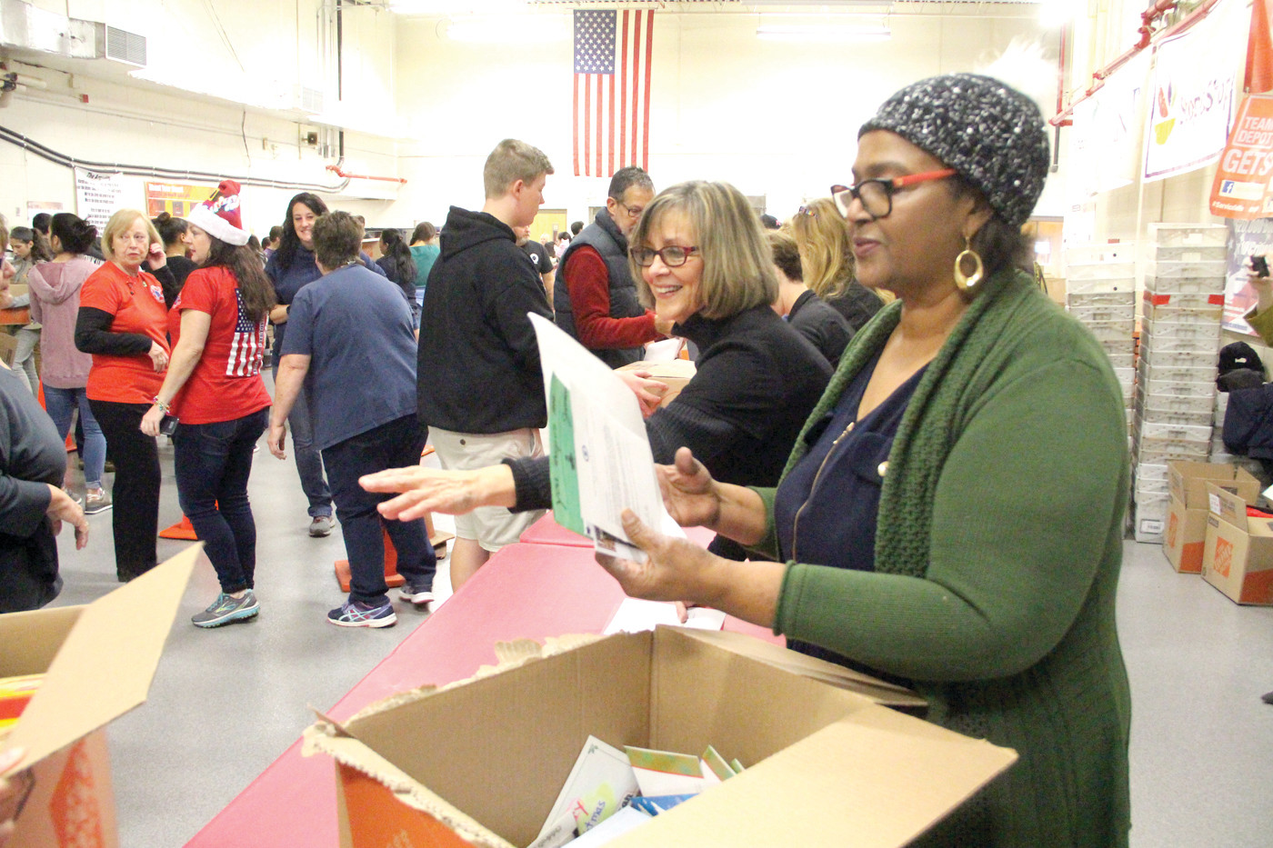 LETTERS FROM HOME: Paulette Hamilton and Rosa DeCastillo, both from the Lt. Governor's office, were the last stop on the assembly line. They made sure each box contained letters written by school children.