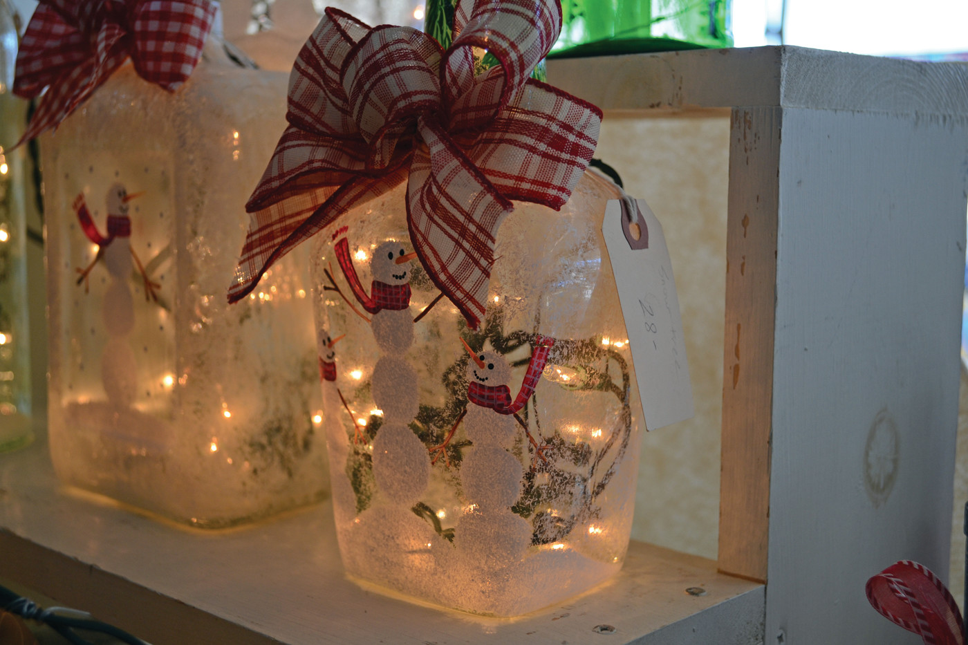 LIGHT UP THE SEASON: A display from Rhode Island Light Bottles, a Chepachet-based artisanal business owned by Kim Belleavoine, utilizes empty bottles of various types to make holiday-inspired, battery-operated, light-up showpieces.