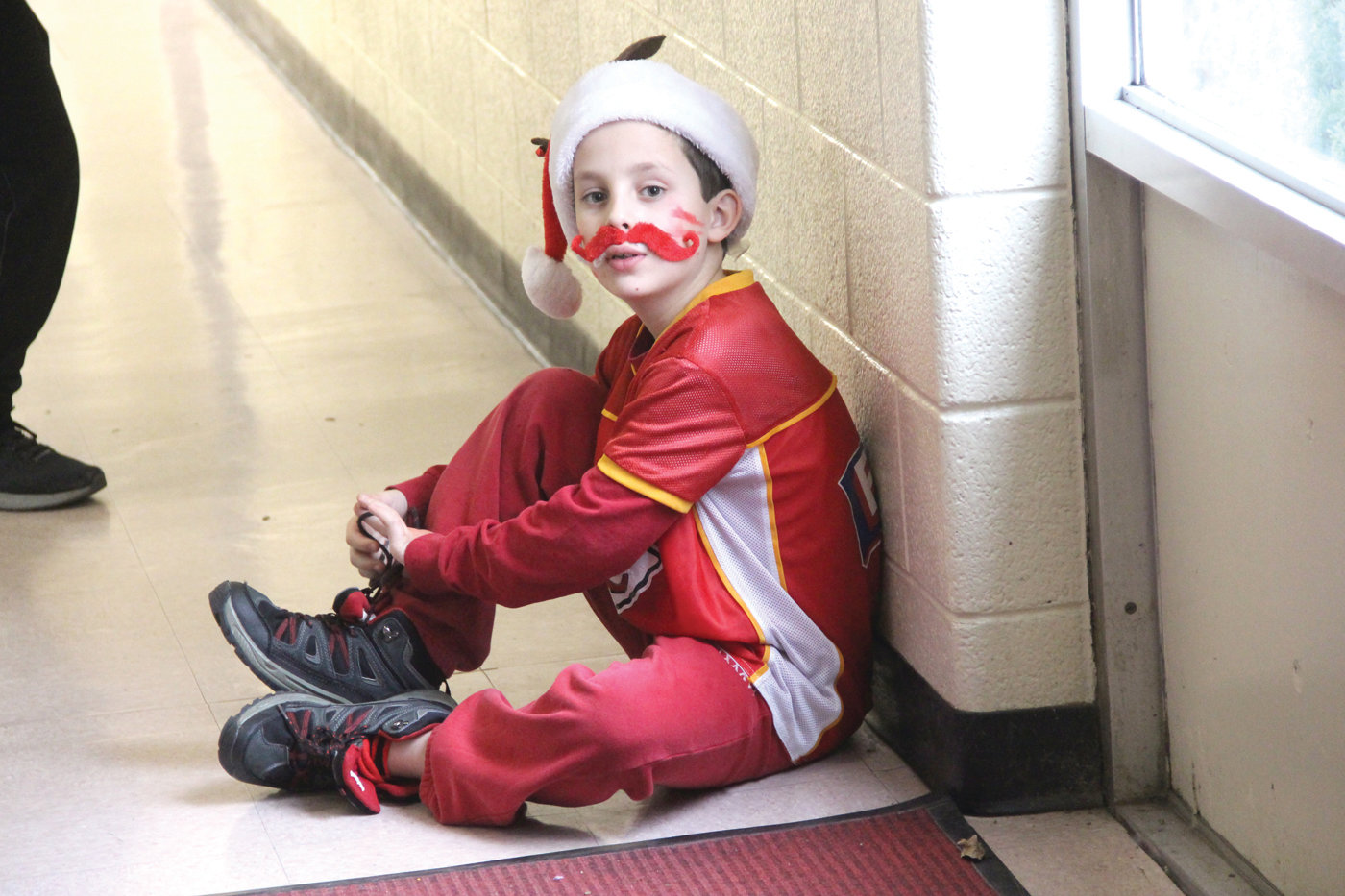 ALL IN RED: Fifth grader Brendan Flynnties his shoes before joining his classmates – all dressed in red – for a school photo.
