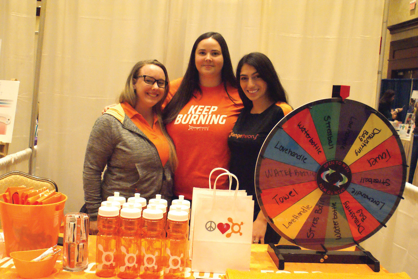 ORANGE IS THE COLOR: Pictured are (l-r) Kayla Perrin, Melanie Plankey and Taya Piccione from Orange Theory Fitness located in Cranston at the Rhode Island Women's Expo held this year at the Crowne Plaza.