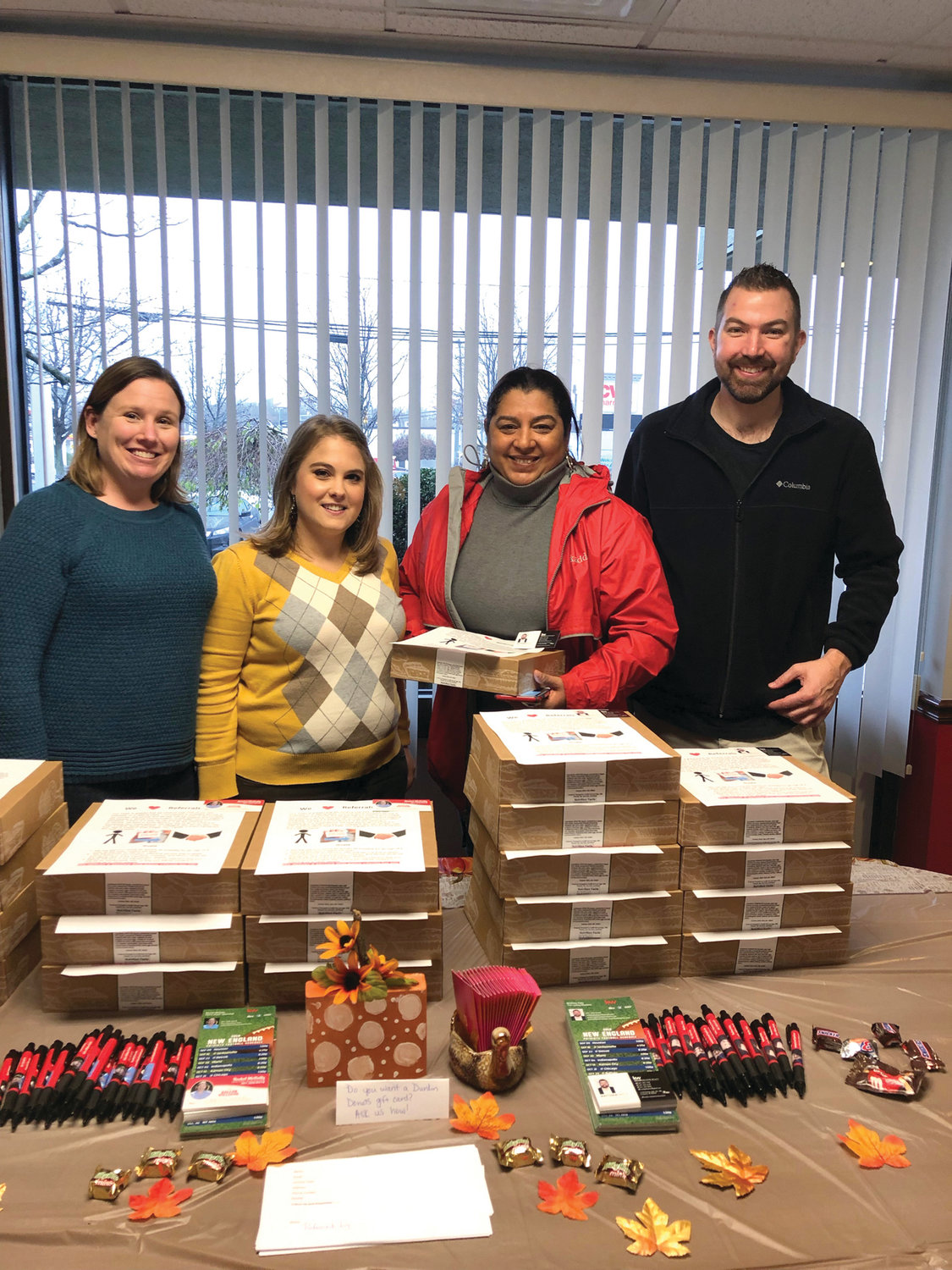 PATTY'S PIES:  Members of the Matt Patty Keller Williams team, Rachel McNally, Katherine Berryman administrator, client Rosaura Polanco and Matt Patty pose in front of all the client pies ready for the taking at the Keller Williams Cranston office on Pontiac Avenue.