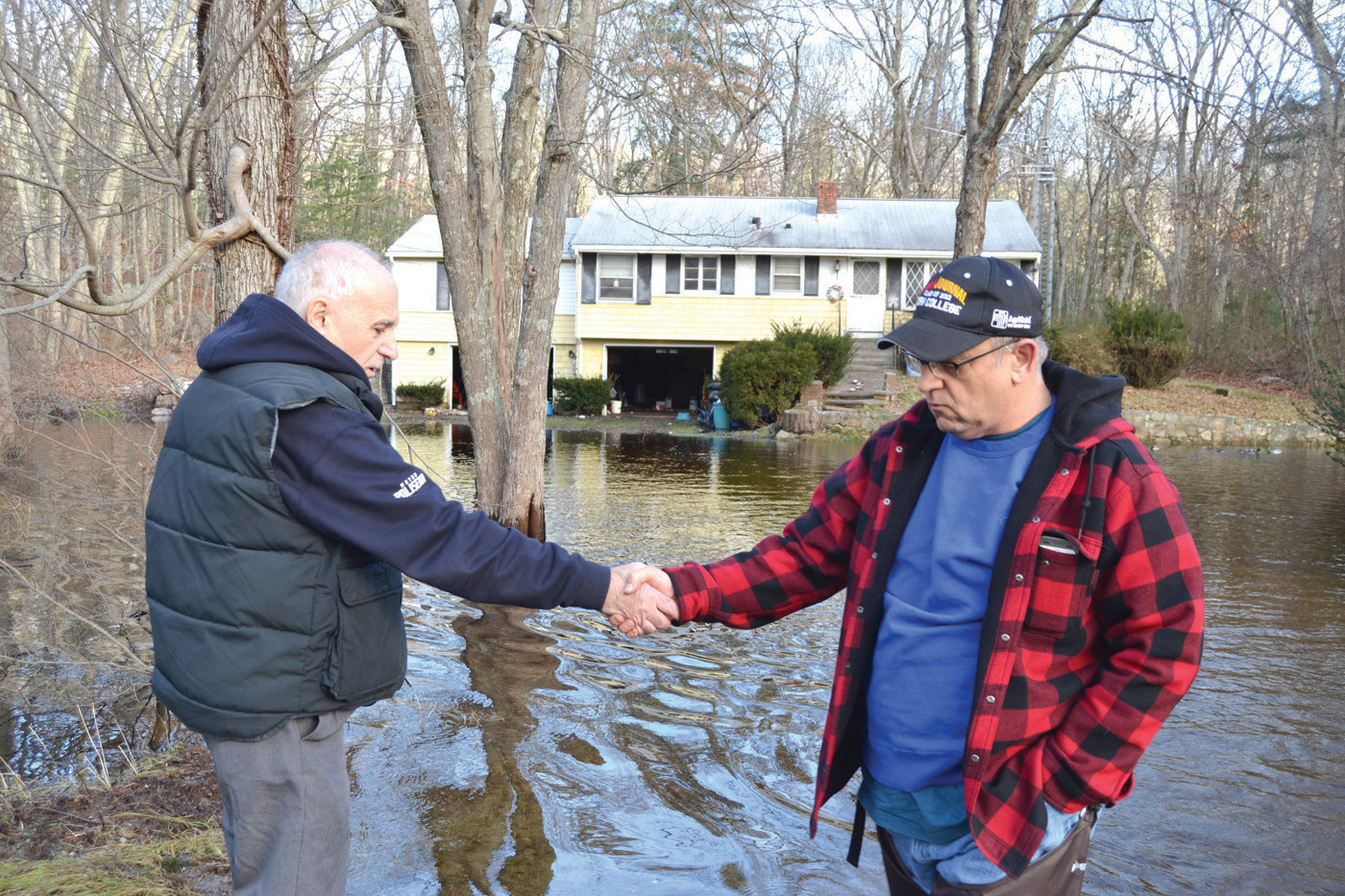 HANDSHAKE IN THE FLOOD:  Mayor Joseph Polisena met with Robert Barcellos outside of his flooded home on Belfield Drive on Tuesday. Barcellos said that after suffering through two floods, he's going to accept a federal buyout offer.