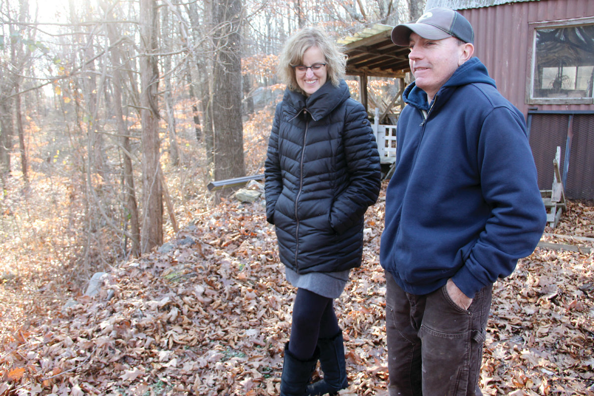 WOODS NOW: Carol and Carl Swanson look out on the wooded property of their neighbor. If the land becomes the site of Cranston's newest solar farm, it will be clear-cut for arrays of solar panels.